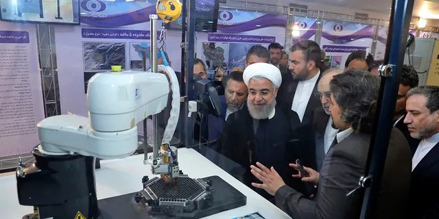 Iran's President Hassan Rouhani listens to explanations on new nuclear achievements at a ceremony to mark
