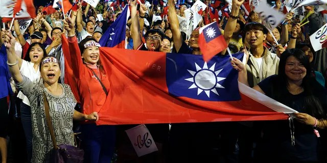 FILE - In this Nov. 24, 2018, file photo, supporters of the opposition Nationalist Party cheer in Kaohsiung, Taiwan. (AP Photo/File)