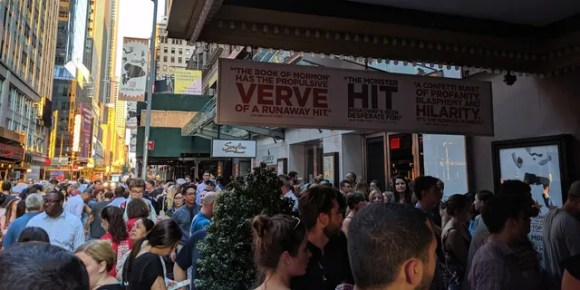 Theatergoers gather under darkened marquees on Broadway.