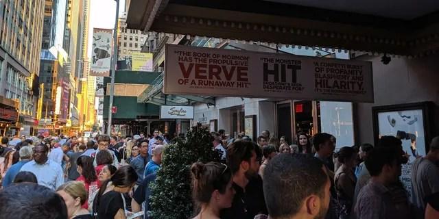 Theatergoers gather under darkened marquees on Broadway.