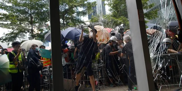 A protester tries to break the glass to get into the Legislative Council in Hong Kong Monday, July 1, 2019.