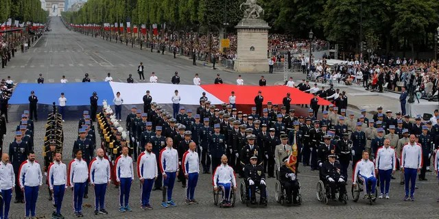 Veterans walk on the Champs-Elysees avenue during the Bastille Day parade in Paris, France, Sunday, July 14, 2019.