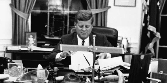 John F. Kennedy Jr. exploring his father's desk.
