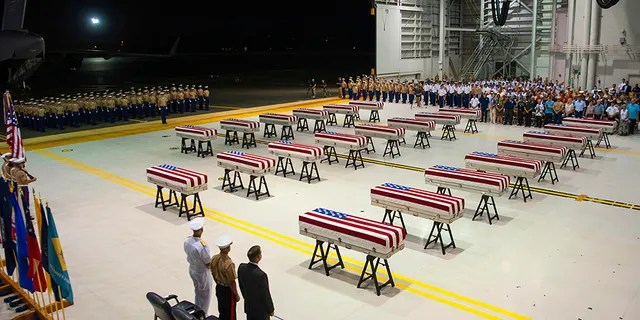 "Service members and guests stand as ""Taps"" is played over transfer cases carrying the remains of unidentified service members lost in the Battle of Tarawa during World War II."