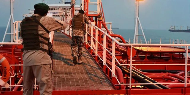 Two armed members of Iran's Revolutionary Guard inspect the British-flagged oil tanker Stena Impero, which was seized in the Strait of Hormuz on Friday by the Guard, in the Iranian port of Bandar Abbas. (AP/Mehr News Agency)