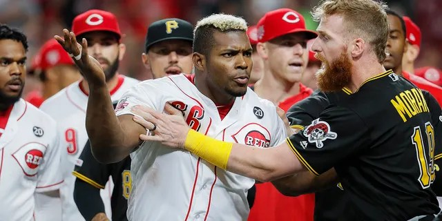 Cincinnati Reds' Yasiel Puig (66) is restrained by Pittsburgh Pirates third baseman Colin Moran (19) during the ninth inning of a baseball game Tuesday, July 30, 2019, in Cincinnati. (Associated Press)