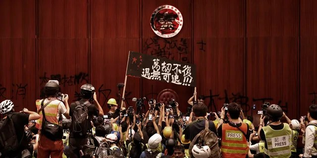 Protesters raise a banner reads