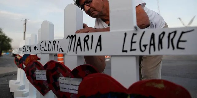 Greg Zanis prepares crosses to place at a makeshift memorial for victims of a mass shooting at a shopping complex Monday in El Paso, Texas. (AP Photo/John Locher)