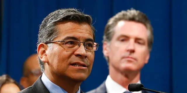 FILE: California Attorney General Xavier Becerra, left, accompanied by Gov. Gavin Newsom, discusses the lawsuit the state has filed against the Trump administration's new rules blocking green cards for many immigrants who receive government assistance.