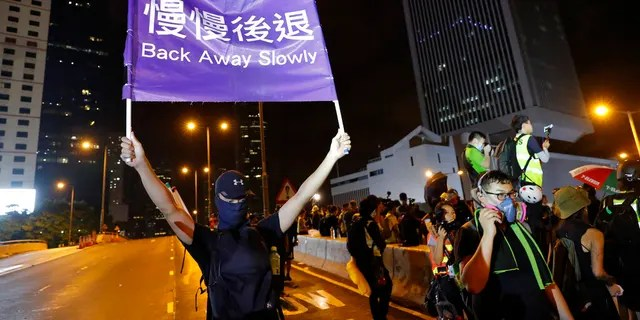 """A demonstrator holding up a sign reading """"Back away slowly"""" to encourage other demonstrators to leave, near the Chinese Liaison Office in Hong Kong on Sunday. (AP Photo/Vincent Thian)"""