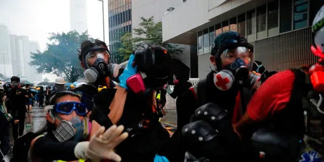 Protestors carry an injured to safety in Hong Kong, Saturday, Aug. 31, 2019. Many of the protesters outside Hong Kong government headquarters have retreated as large contingents of police arrive on the streets in what looks like preparation for a clearing operation. Police were using tear gas Saturday to drive back remaining protesters.