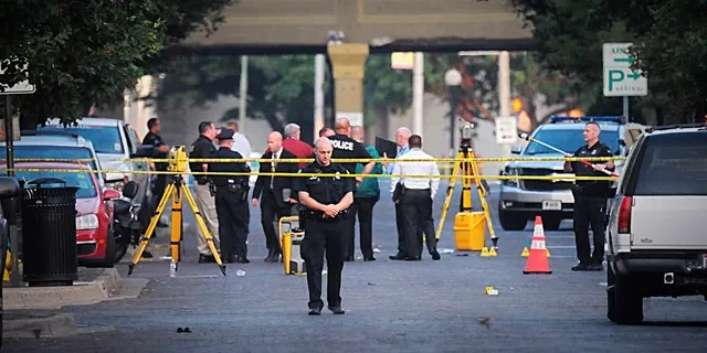 Dayton police look for evidence after a mass shooting in Dayton, Ohio on Sunday, Aug, 4, 2019.