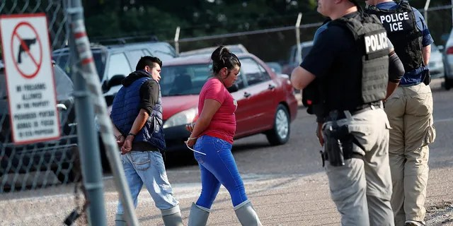 Two people are taken into custody at a Koch Foods Inc. plant in Morton, Miss., Wednesday. (AP Photo/Rogelio V. Solis)