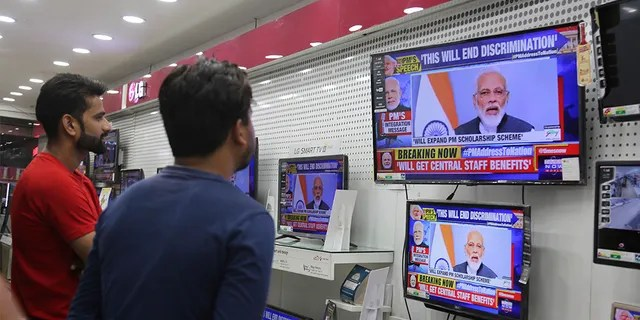 Indians watch Prime Minister Narendra Modi address the nation in an electronics store Thursday. (AP Photo/Channi Anand)