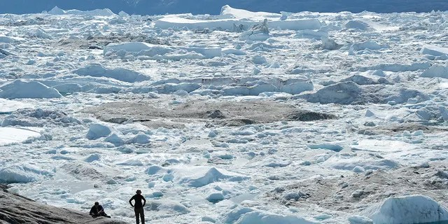 File photo: Visitors look out onto free-floating ice jammed into the Ilulissat Icefjord during unseasonably warm weather on July 30, 2019 near Ilulissat, Greenland. The Sahara heat wave that recently sent temperatures to record levels in parts of Europe is arriving in Greenland.  (Photo by Sean Gallup/Getty Images)