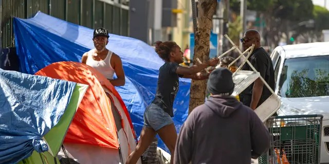 A homeless woman throwing a plastic chair in the air in downtown Los Angeles on Tuesday. Los Angeles Mayor Eric Garcetti said he hoped President Trump will work with the city to end homelessness. (AP Photo/Damian Dovarganes)