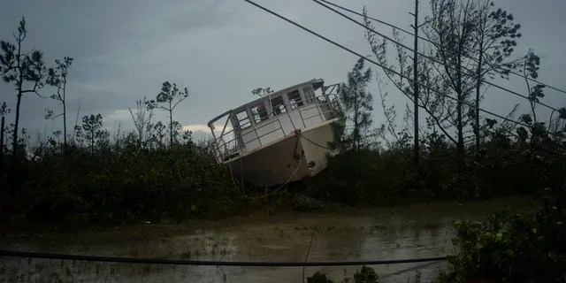 A boat thrown onshore by the Hurricane Dorian lays stranded next to a highway near Freeport, Grand Bahama, Bahamas, Tuesday Sept. 3, 2019.