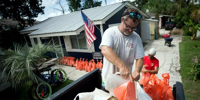Joey Spalding, left, fills sandbags with the help of his friend Tom Sikes, right, at Spalding's home in Tybee Island, Ga., Tuesday, Sept. 3, 2019, before the potential arrival of Hurricane Dorian.