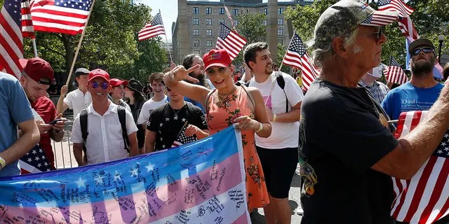 A transgender Trump supporter, center, marches in the Straight Pride Parade in Boston, Saturday, Aug. 31, 2019. (AP Photo/Michael Dwyer)