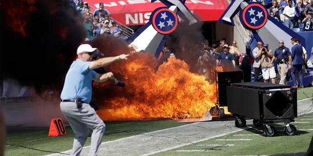 A fire from a pyrotechnics machine burning on the field before the game between the Tennessee Titans and the Indianapolis Colts on Sunday. (AP Photo/James Kenney)