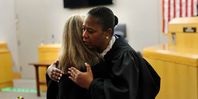 State District Judge Tammy Kemp gives former Dallas Police Officer Amber Guyger a hug before Guyger leaves for jail, Wednesday, Oct. 2, 2019, in Dallas. Guyger, who said she mistook neighbor Botham Jean's apartment for her own and fatally shot him in his living room, was sentenced to a decade in prison. (Tom Fox/The Dallas Morning News via AP, Pool)