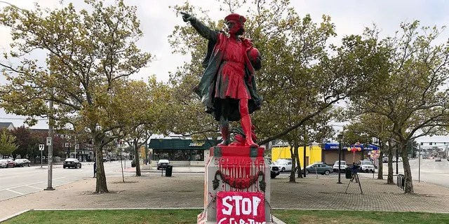 """A sign reading """"stop celebrating genocide"""" sits at the base of a statue of Christopher Columbus on Monday in Providence, Rhode Island, after it was vandalized with red paint on the day named to honor him as one of the first Europeans to reach the New World. (AP Photo/Michelle R. Smith)"""