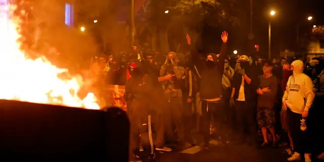 Protestors stand by a burning barricade in Barcelona, Spain, Saturday, Oct. 19, 2019. Radical separatists have clashed with police each night in Barcelona and other Catalan cities following huge peaceful protests of people angered by Monday's Supreme Court verdict that sentenced nine separatist leaders to prison. (AP Photo/Emilio Morenatti)