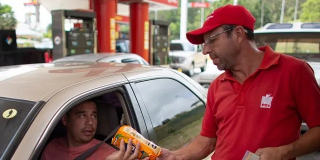 In this Oct. 8, 2019 photo, gas station attendant Orlando Godoy takes a package of corn flour as payment after filling a motorist's tank, which costs a tiny fraction of a U.S. penny, in San Antonio de los Altos on the outskirts of Caracas, Venezuela. The economy is in such shambles that drivers are now paying for fill-ups with a little food, a candy bar or just a cigarette. (AP Photo/Ariana Cubillos)