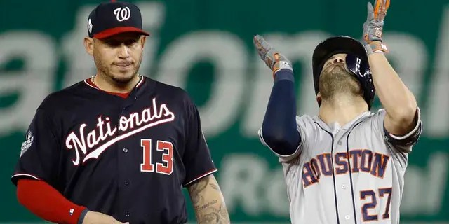 Houston Astros' Jose Altuve, right, celebrates next to Washington Nationals second baseman Asdrubal Cabrera after a double during the fifth inning of Game 3 of the baseball World Series Friday, Oct. 25, 2019, in Washington. (Associated Press)