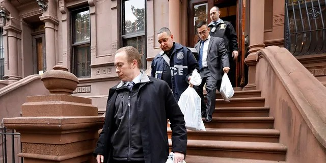 New York City Police Department personnel carry bags from a residential building in New York's Harlem neighborhood, Thursday, Nov. 7, 2019. (Associated Press)