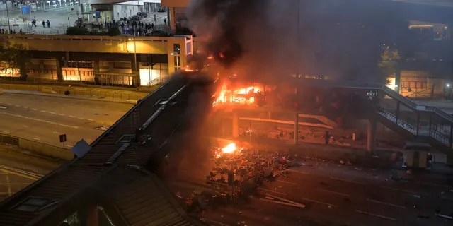 A fire burns on a bridge occupied by protestors over a highway leading to the Cross Harbour Tunnel in Hong Kong, Sunday, Nov. 17, 2019.