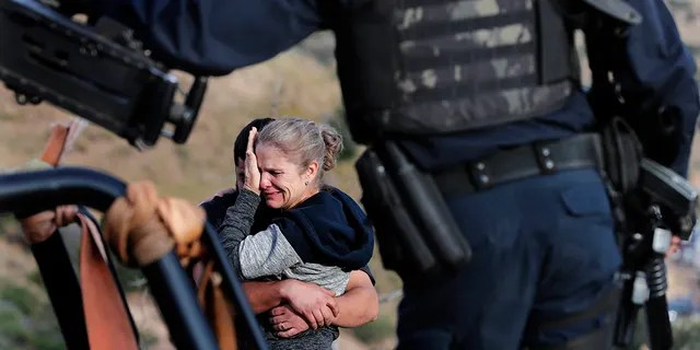 Framed by heavily armed Mexican authorities, relatives of the LeBaron family mourn at the site where nine U.S. citizens, three women and six children related to the extended LeBaron family, were slaughtered when cartel gunmen ambushed three SUVs along a dirt road near Bavispe, at the Sonora-Chihuahua border, Mexico, Wednesday, Nov 6, 2019. (Associated Press)