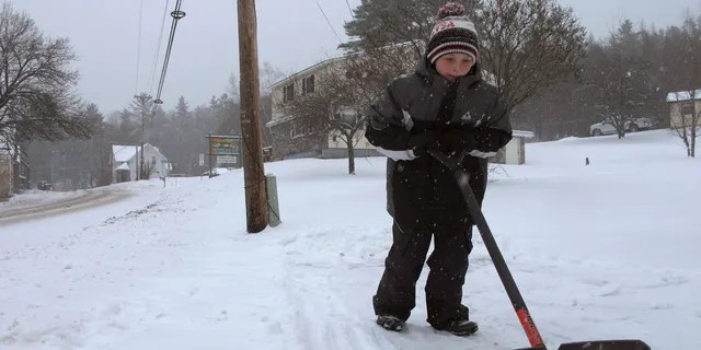 Kaiden Rogers shovels snow from his driveway on Tuesday, Nov. 12, 2019 in Marshfield, Vt.