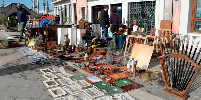 Sketches and drawings are lined up to dry up outside an art store following a flooding in Venice, Italy, Thursday, Nov. 14, 2019.
