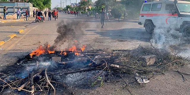 Protesters set fire to close a street in Sadr City during the ongoing anti-government protests in Baghdad, Iraq, on Monday. (AP)