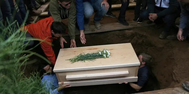 The coffin containing the remains of 12-year-old Howard Jacob Miller Jr. was lowered into a grave on Friday. (Associated Press)