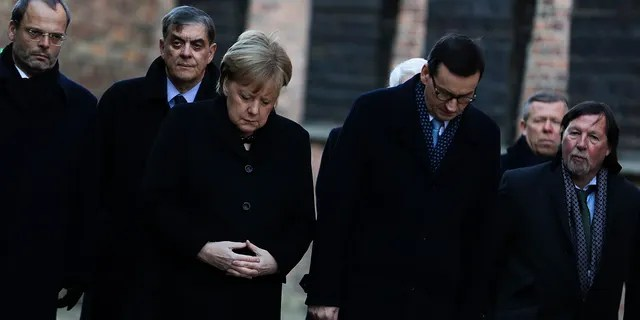 German Chancellor Angela Merkel, center left, and Polish Prime Minister Mateusz Morawiecki, center right, attend a wreath-laying ceremony at the death wall in the former Nazi death camp of Auschwitz-Birkenau in Oswiecim, Germany, Friday, Dec. 6, 2019. Merkel visits the former death camp in the occasion of the 10th anniversary of the founding of the Auschwitz Foundation.