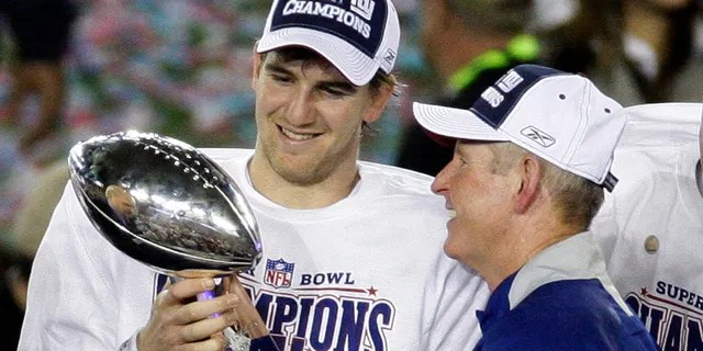 New York Giants quarterback Eli Manning, left, and coach Tom Coughlin look at the Vince Lombardi Trophy as they celebrate after the Giants beat the New England Patriots 17-14 in the 2008 Super Bowl in Glendale, Ariz.