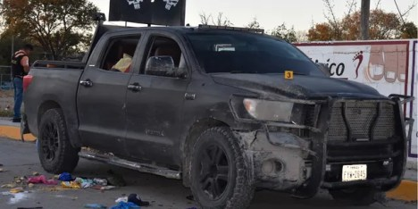 A damaged pick up is on a street of Villa Union, Mexico, after a gun battle between Mexican security forces and suspected cartel gunmen on Saturday.