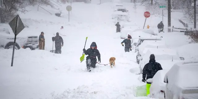 Neighbors work together in an effort to clear out as much snow as possible from E. 8th Street, Sunday, Dec. 1, 2019, in Duluth, Minn.
