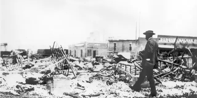 Photograph of an African-American man with a camera looking at the skeletons of iron beds which rise above the ashes of a burned-out block after the Tulsa Race Riot, Tulsa, Oklahoma, 1921.
