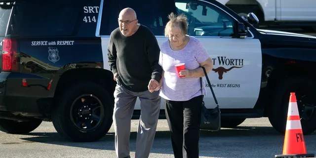An elderly couple walks from West Freeway Church of Christ hours after a fatal shooting at the church, Sunday, Dec. 29, 2019, in White Settlement, Texas.