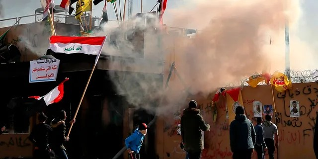 Pro-Iranian militiamen and their supporters set a fire while U.S. soldiers fired tear gas during a sit-in in front of the U.S. embassy in Baghdad, Iraq, Wednesday, Jan. 1, 2020. (AP Photo/Khalid Mohammed)