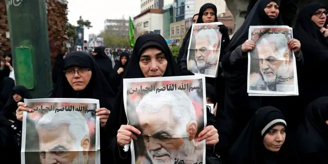 """Protesters hold up posters of Gen. Qassem Soleimani while mourning during a demonstration over the U.S. airstrike in Iraq that killed Iranian Revolutionary Guard Gen. Qassem Soleimani, in Tehran, Iran, Saturday Jan. 4, 2020. Iran has vowed """"harsh retaliation"""" for the U.S. airstrike near Baghdad's airport that killed Tehran's top general and the architect of its interventions across the Middle East, as tensions soared in the wake of the targeted killing. (AP Photo/Ebrahim Noroozi)"""