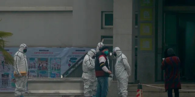 Staff in biohazard suits hold a metal stretcher by the in-patient department of Wuhan Medical Treatment Center, where some infected with a novel coronavirus are being treated.