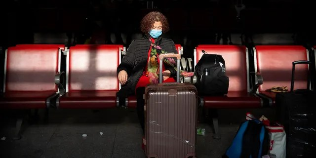 A traveler wears a face mask as she sits in a waiting room at Beijing West Railway Station in Beijing, Tuesday, Jan. 21, 2020.