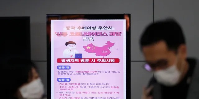 """A poster warning about coronavirus is seen as passengers wear masks in a departure lobby at Incheon International Airport in Incheon, South Korea, Monday, Jan. 27, 2020. China on Monday expanded sweeping efforts to contain a viral disease by extending the Lunar New Year holiday to keep the public at home and avoid spreading infection. The sign reads """" A new coronavirus occurs in Wuhan City, China."""" (AP Photo/Ahn Young-joon)"""