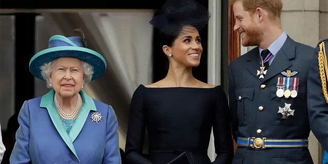 Queen Elizabeth II of Great Britain, left, and Meghan the Duchess of Sussex and Prince Harry watch a parade of Royal Air Force planes pass over Buckingham Palace in London (AP Photo / Matt Dunham, File)