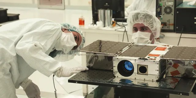 Left to right: Electrical Test Engineer Esha Murty and Integration and Test Lead Cody Colley prepare the ASTERIA spacecraft for mass-properties measurements in April 2017 prior to spacecraft delivery ahead of launch. ASTERIA was deployed from the International Space Station in November 2017. Credit: NASA/JPL-Caltech
