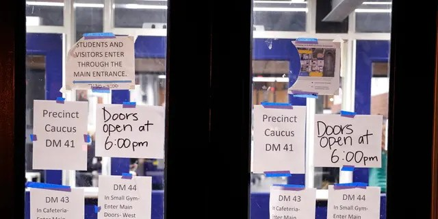 Directional signs are posted on doors at a caucus at Roosevelt Hight School, Monday, Feb. 3, 2020, in Des Moines, Iowa. (AP Photo/Andrew Harnik)